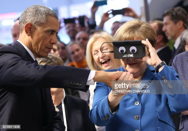 TOPSHOT German chancellor Angela Merkel looks through a device next to US President Barack Obama at the booth of German automation company ifm...