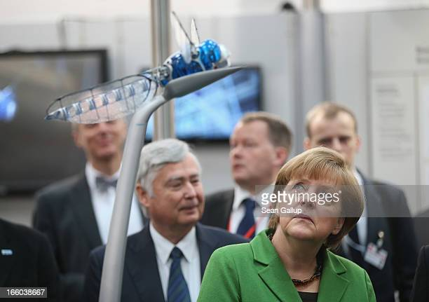 German Chancellor Angela Merkel looks up at a remotecontrolled drone called a BionicOpter that looks like a dragonfly at the Festo stand at the...
