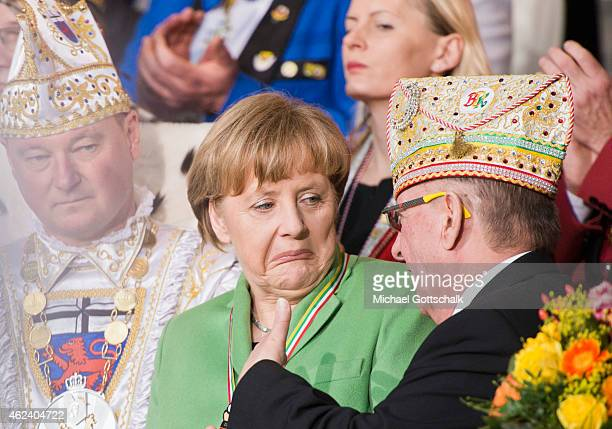 German Chancellor Angela Merkel makes a grimace during a chat with Volker Wagner head of Bund Deutscher Karneval during a reception for members of...