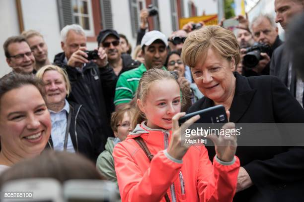 German Chancellor Angela Merkel makes a selfie with a girl near Speyer cathedral prior a requiem of a former German Chancellor Helmut Kohl on July 1...