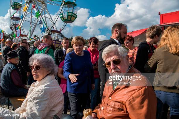 German Chancellor Angela Merkel makes her way to greet people at a neighbourhood fair organised by the local branch of the Christian Democratic Union...