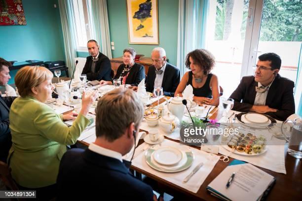 German Chancellor Angela Merkel meets representatives of civil society including Camel Daoud Nadia AitZai Miloud Brahimi Sofia Djama and Said Salhi...