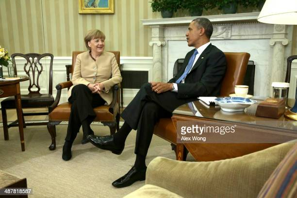 German Chancellor Angela Merkel meets with US President Barack Obama in the Oval Office of the White House May 2 2014 in Washington DC Obama and...