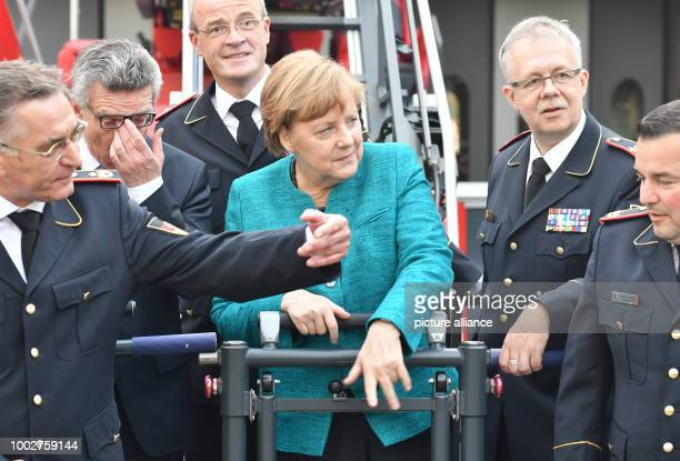 German Chancellor Angela Merkel next to Federal Minister of the Interior Thomas de Maizière waves to firefighters so that they join her for a picture...