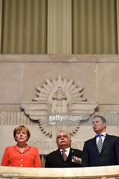 German Chancellor Angela Merkel NSW President of the RSL Don Rowe and Federal Minister Josh Frydenberg pause for a moments silence as they look into...