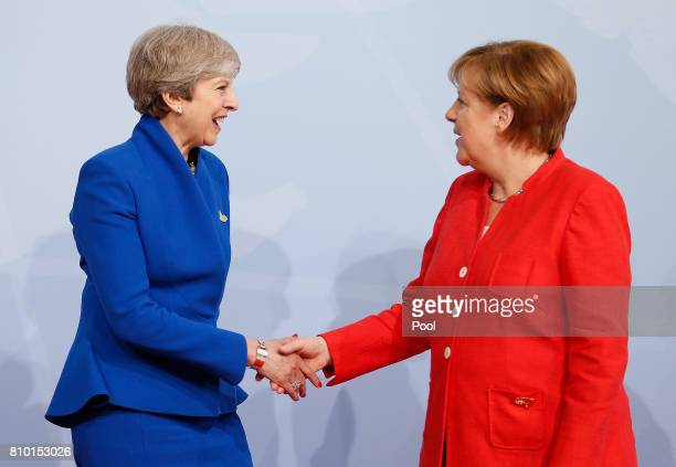 German Chancellor Angela Merkel officially welcomes officially welcomes British Prime Minister Theresa May to the opening day of the G20 summit on...