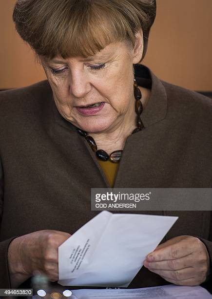 German Chancellor Angela Merkel opens an envelope at the start of the weekly cabinet meeting at the Chancellery in Berlin on October 28 2015 AFP...