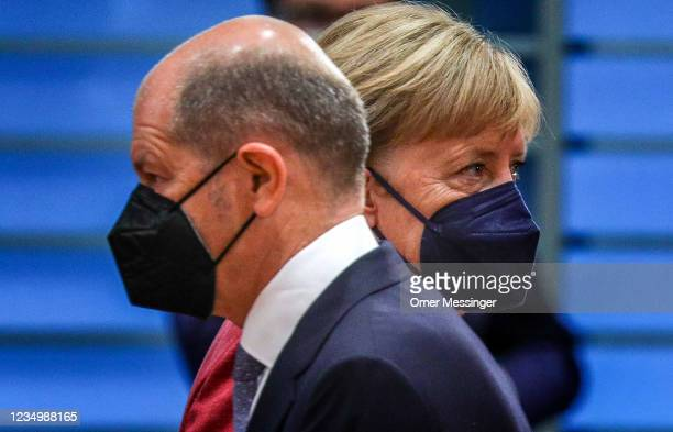 German Chancellor Angela Merkel passes by German Minister of Finance Olaf Scholz at the weekly government cabinet meeting on September 1, 2021 in...