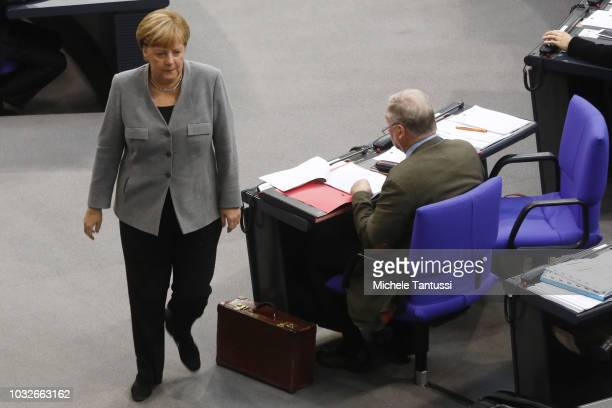 German Chancellor Angela Merkel passes by the far right party AfD leader Alexander Gauland as she leaves a session of the German Parliament or...