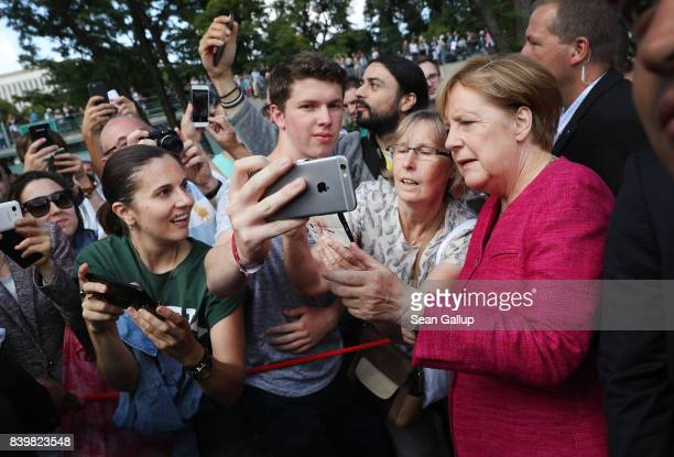 German Chancellor Angela Merkel pauses for a selfie among visitors during the annual openhouse day at the Chancellery on August 27 2017 in Berlin...
