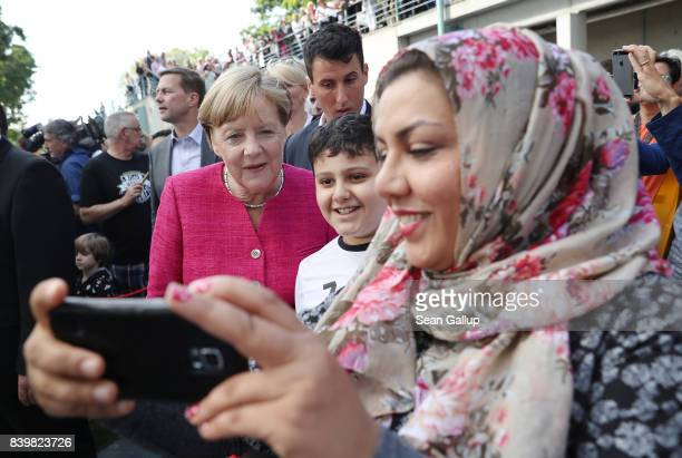 German Chancellor Angela Merkel pauses for a selfie with a Muslim family among visitors during the annual openhouse day at the Chancellery on August...
