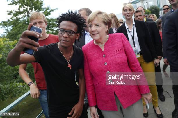 German Chancellor Angela Merkel pauses for a selfie with a young man who came alone as a refugee from Eritrea to Germany among visitors during the...