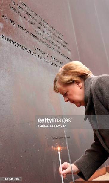 German Chancellor Angela Merkel places a candle at the Berlin Wall Memorial during the central commemoration ceremony for the 30th anniversary of the...
