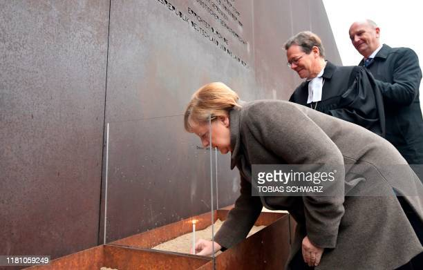 German Chancellor Angela Merkel places a candle at the Berlin Wall Memorial as Markus Droege , bishop of the Evangelical Church...