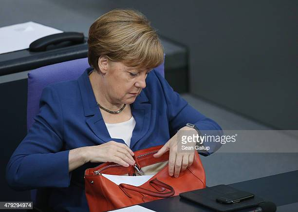 German Chancellor Angela Merkel places an item into her handbag while she attends a session of the Bundestag on July 3 2015 in Berlin Germany The...