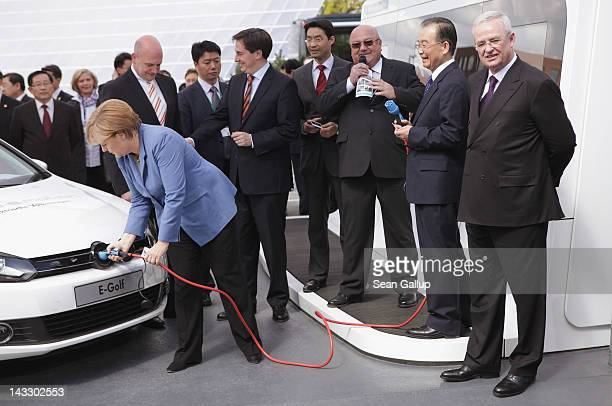 German Chancellor Angela Merkel plugs in a Volkswagen electric car as Chinese Premier Wen Jiabao Volkswagen CEO Martin Winterkorn and Lower Saxony...