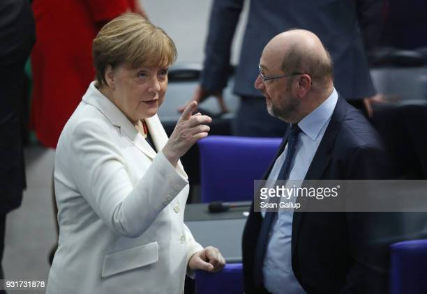German Chancellor Angela Merkel points to her mother while chatting with Social Democrat Martin Schulz who ran against her in elections last year...