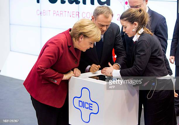 German Chancellor Angela Merkel, Polish Prime Minister Donald Tusk and Stephan Weil, Prime Minister of Lower Saxony look at the electronic dice DICE+...