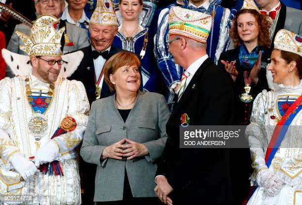German Chancellor Angela Merkel poses for a group photo as she receives royal couples of the federal German states during the carnival reception at...