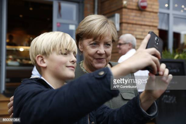 German Chancellor Angela Merkel poses for a selfie photo with a boy before addressing an election campaign rally of the Christian Democratic Union in...