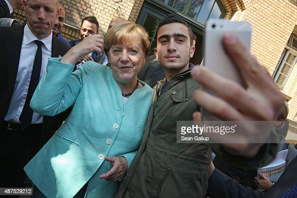German Chancellor Angela Merkel poses for a selfie with Anas Modamani, a refugee from Syria, after she visited the AWO Refugium Askanierring shelter...