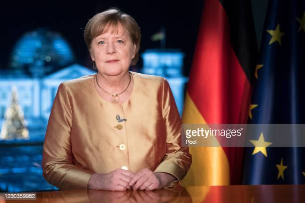 German Chancellor Angela Merkel poses for photographs after the television recording of her annual New Year's speech at the chancellery on December...
