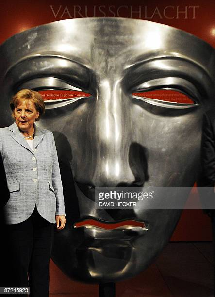 """German Chancellor Angela Merkel poses in front of a reproduction of a Roman horseman's mask during the opening of an exhibition """"Imperium Conflict..."""
