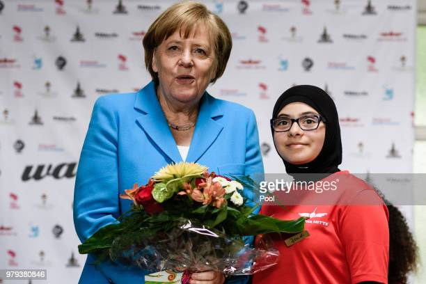 German Chancellor Angela Merkel poses with a young member of the sports club 'SV RotWeiss Viktoria Mitte 08' Joudi who presented her with some...