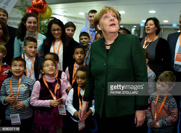 German Chancellor Angela Merkel poses with children during the conservative Christian Democratic Union party's congress in Essen western Germany on...