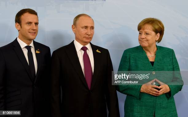 German Chancellor Angela Merkel poses with French President Emmanuel Macron and Russia's President Vladimir Putin prior to a meeting during the G20...