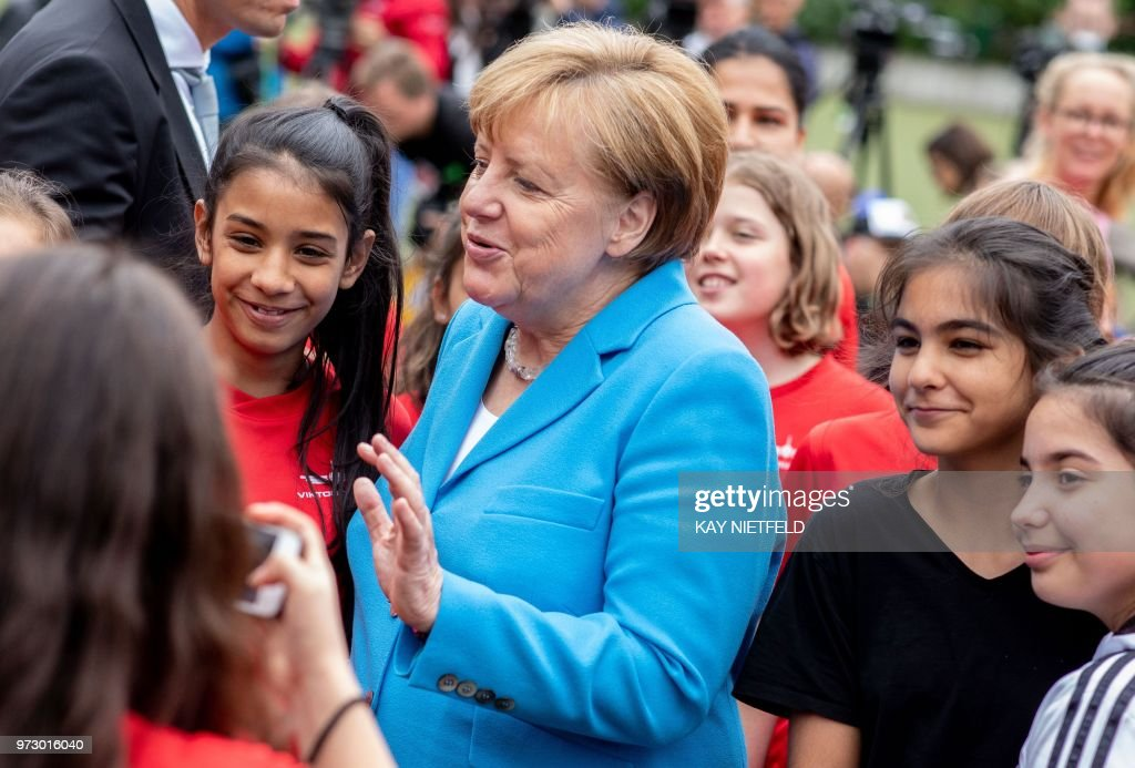 German Chancellor Angela Merkel (C) poses with girls taking part in the event 'Sports and Integration' as she visits the 'SV Rot-Weiß Viktoria Mitte 08' sports club in Berlin on June 13, 2018, prior to the German government's integration summit. (Photo by Kay Nietfeld / dpa / AFP) / Germany OUT