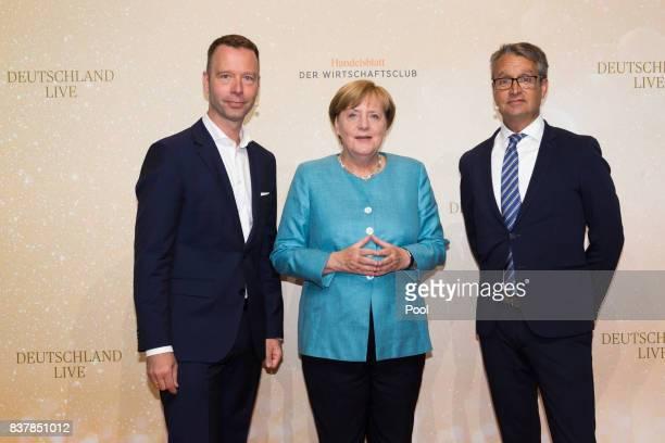 German Chancellor Angela Merkel poses with Handelsblatt chief editor Sven Afhüppe and Handelsblatt editor Gabor Steingart at Germany Live Where does...