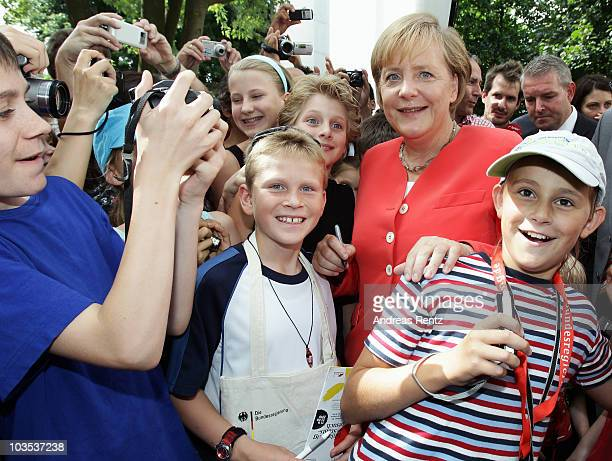 German Chancellor Angela Merkel poses with kids at an open house day at the Chancellery on August 22 2010 in Berlin Germany More than 150000 of...