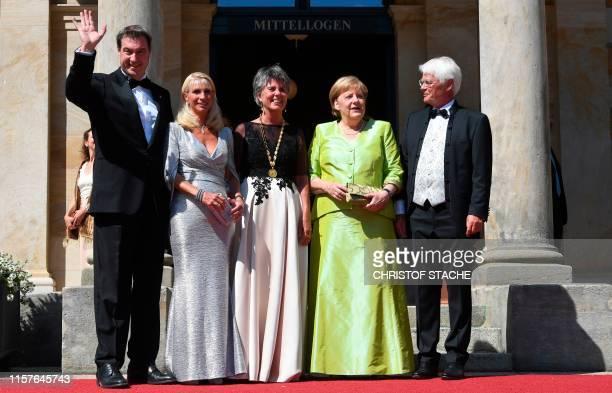 German Chancellor Angela Merkel poses with the mayor of Bayreuth Brigitte Merk-Erbe , her husband Thomas Erbe , Bavaria's State Premier Markus Soeder...