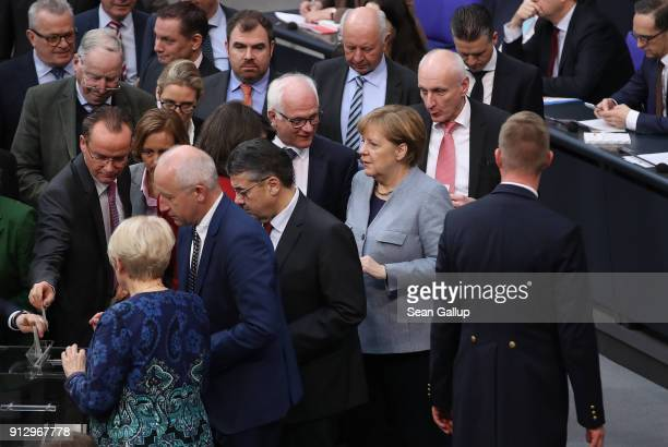 German Chancellor Angela Merkel prepares to cast a ballot at the Bundestag following debates over a proposal concerning the rights of refugees who...