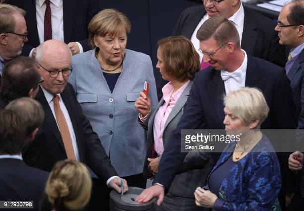 German Chancellor Angela Merkel prepares to cast her ballot as she stands next Beatrix von Storch of the rightwing AfD at the Bundestag following...