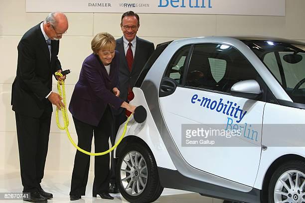 German Chancellor Angela Merkel prepares to plug in an electicpowered Smart car as Daimler head Juergen Zetsche and Matthias Wissmann Chairman of the...