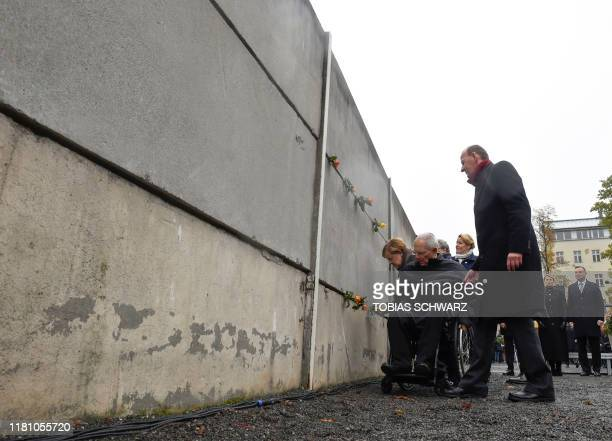 German Chancellor Angela Merkel President of the Bundestag Wolfgang Schaeuble place flowers at the Wall Memorial as Polish President Andrzej Duda and...