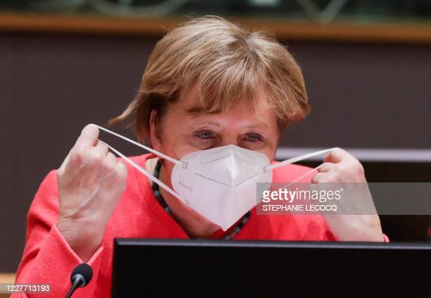 TOPSHOT German Chancellor Angela Merkel puts her mask on during a last roundtable discussion following a four days European summit at the European...