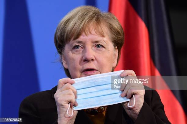 German Chancellor Angela Merkel puts on her mask after a joint press conference with German Health Minister Jens Spahn at the chancellery on March...