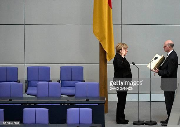German Chancellor Angela Merkel raises her hand as she is sworn in by President of German lower house of Parliament Bundestag Norbert Lammert after...