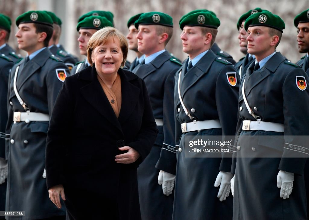 German Chancellor Angela Merkel reacts after greeting the honor guard, prior to the arrival of Libya's Prime Minister Fayez al-Sarrajwalk at the Chancellery in Berlin on December 7, 2017. PHOTO / John MACDOUGALL