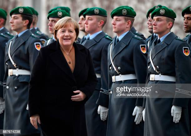 German Chancellor Angela Merkel reacts after greeting the honor guard, prior to the arrival of Libya's Prime Minister Fayez al-Sarrajwalk at the...