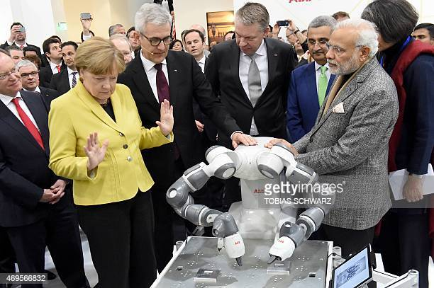 German Chancellor Angela Merkel reacts after touching the collaborative dualarm robot YuMi next to Indian Prime Minister Narendra Modi at the Swiss...