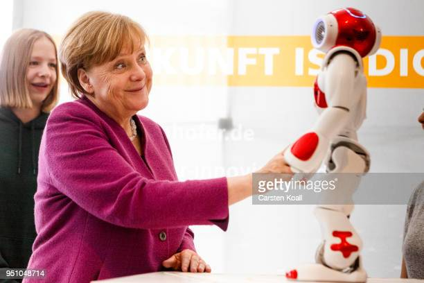 German Chancellor Angela Merkel reacts in front of a robot as she visits a stand of the Frauenhofer Institut during the annual Girls' Day at the...