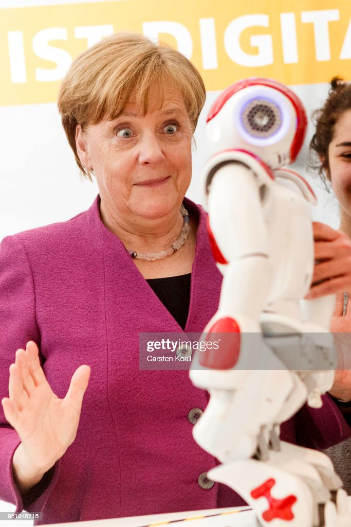 German Chancellor Angela Merkel reacts in front of a robot as she visits a stand of the Frauenhofer Institut during the annual Girls' Day at the Chancellery on April 25, 2018 in Berlin, Germany. Government ministries and private employers across Germany participate in the annual event, now in its 18th year, which is meant to encourage young girls to consider a full range of options for their future.