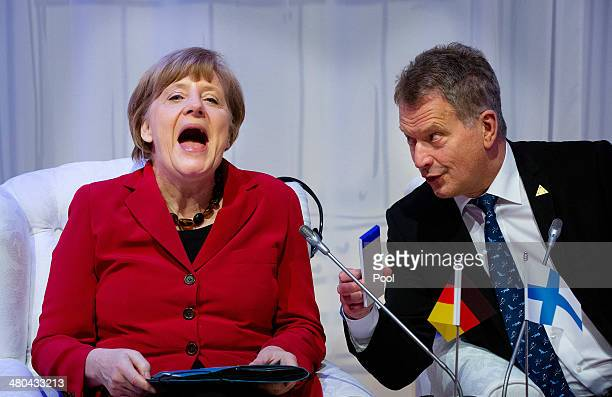 German Chancellor Angela Merkel reacts next to President of Finland Sauli Niinisto during the 2014 Nuclear Security Summit on March 25 2014 in The...
