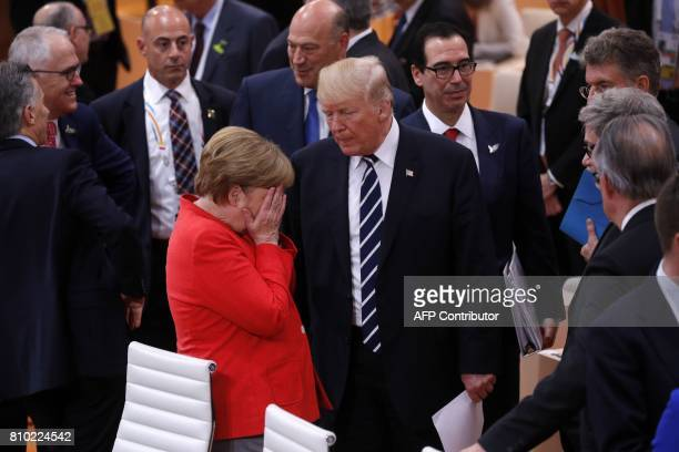 German Chancellor Angela Merkel reacts next to US President Donald Trump at the start of the first working session of the G20 meeting in Hamburg,...