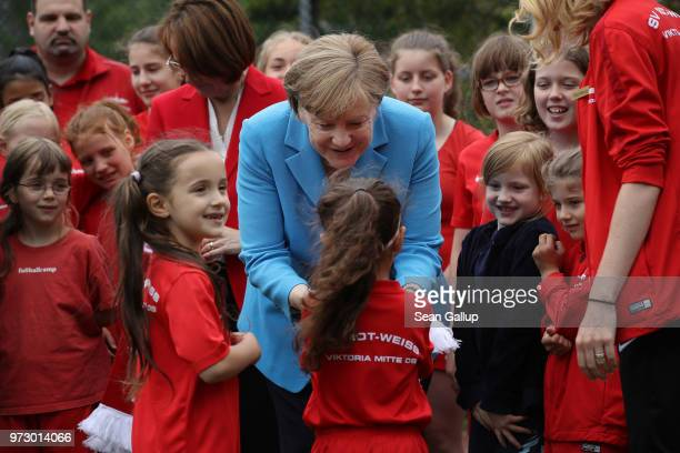 German Chancellor Angela Merkel receives a gift at the conclusion of her visit to a program to encourage integration of children with foreign roots...