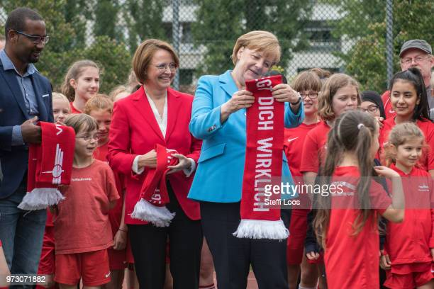 German Chancellor Angela Merkel receives a scarf from young girls during a visit of a program to encourage integration of children with foreign roots...
